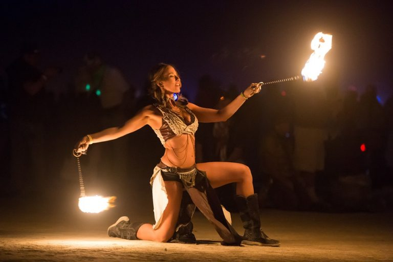 Künstlerin beim Tanzen mit Feuer nach dem Konsum einer die Sinne schärfenden Cannabissorte